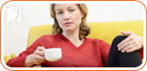 Woman drinking coffee: caffeine may play a role in cyclical breast pain