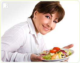 Woman with a salad: a healthy diet can prevent menopausal dizziness